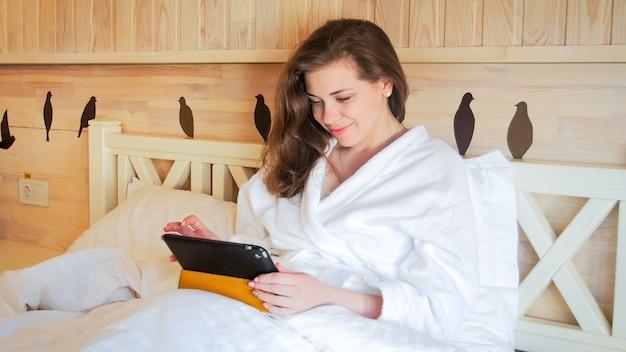 ベッドに横たわってタブレットコンピューターで作業してバスローブで美しい笑顔の女性の肖像画