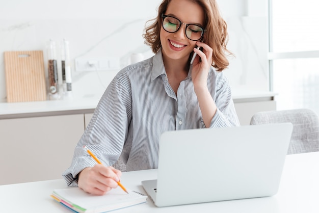 室内で携帯電話で話しながらメモを取るメガネの美しい笑顔の女性の肖像画