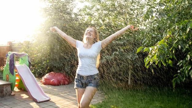 Портрет красивой улыбающейся женщины в мокрой одежде, наслаждаясь теплым дождем в саду заднем дворе дома на закате. девушка играет и развлекается на открытом воздухе летом