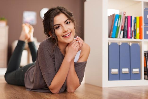 집에서 바닥에 누워 아름 다운 웃는 여자의 초상화