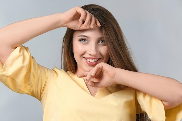 Портрет красивой улыбающейся женщины на светлом фоне