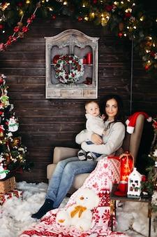 飾られたクリスマスツリーに対して彼女の素敵な赤ちゃんを保持している髪型とメイクアップの美しい笑顔の女性の肖像画