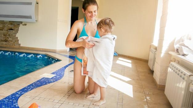 Портрет красивой улыбающейся молодой женщины, укрывающей и вытирающей своего 3-летнего маленького сына после купания в закрытом бассейне