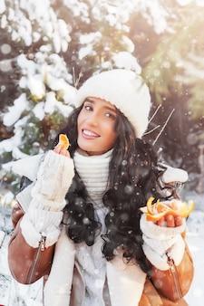 그녀의 손에 익은 귤, 크리스마스 또는 새해 휴일, 겨울 방학 겨울 숲에서 화창한 날에 아름 다운 미소 젊은 여자의 초상화