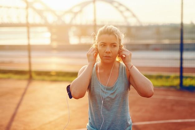이른 아침에 법원에 서있는 동안 귀에 이어폰을 넣어 아름 다운 스포티 한 금발 여자의 초상화.
