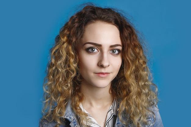 깨끗하고 완벽한 피부와 물결 모양의 가벼운 머리 포즈를 가진 아름다운 학생 소녀의 초상화, 광고 콘텐츠 복사 공간이있는 빈 파란색 벽 벽에 데님 재킷을 입은