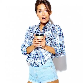 プラスチック製のコーヒーカップを保持している市松模様のシャツで美しいスタイリッシュなクールな10代女性の肖像画