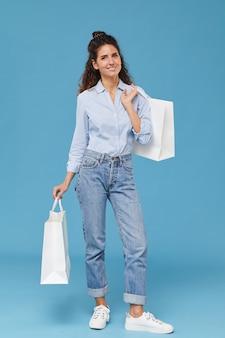 青い背景に買い物袋を持って立って笑っている美しいスタイリッシュな女性の肖像画