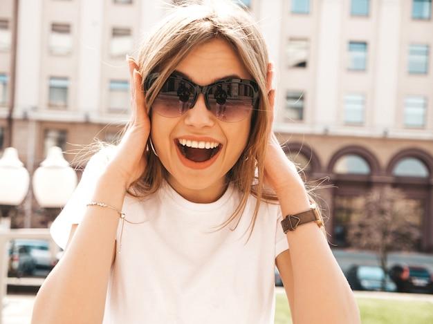 Портрет красивой удивленной белокурой модели оделся в летней одежде хипстера. модная девушка позирует на фоне улицы. смешная потрясенная женщина