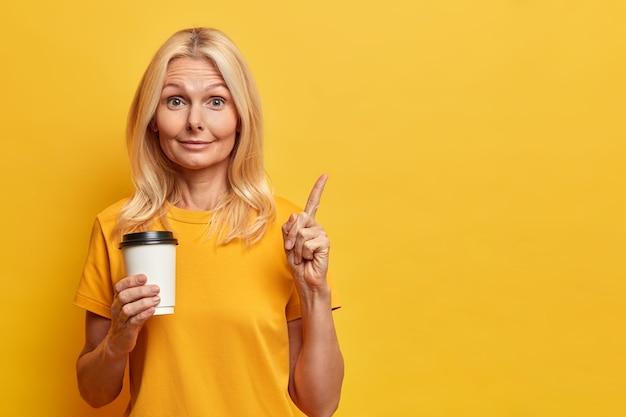 Портрет красивой удивленной женщины указывает в верхнем правом углу, держит кофе на вынос, получает представление во время перерыва, имеет здоровую кожу и светлые волосы