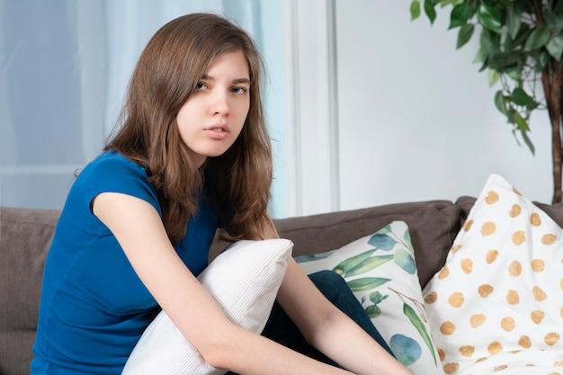 아름 다운 십 대 소녀 젊은 지 루 아름 다운 여자의 초상화는 소파에 거실에서 집에 앉아