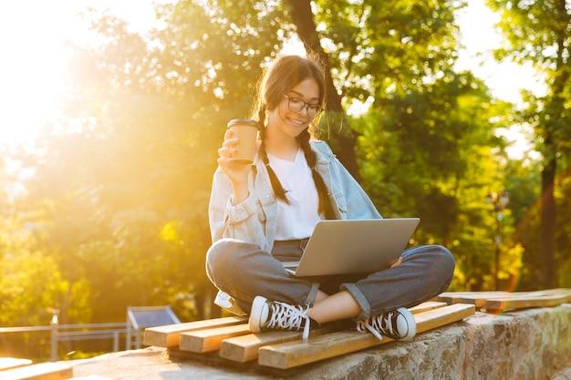 Портрет красивой девушки-подростка в очках, держащей бумажный стаканчик и использующей ноутбук, сидя на скамейке в зеленом парке