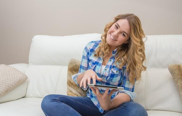 ソファに座ってタブレットpcを使用して美しいティーンエイジャーの肖像画。ホームリラックス、レジャー、テクノロジーのコンセプト。