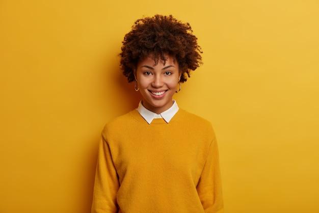 美しい優しい女性の肖像画は陽気な笑顔を持って、白い襟付きのカジュアルなジャンパーを着て、鮮やかな黄色の空間に立ち、カメラを直接見ています