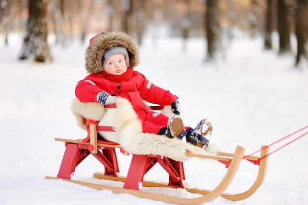 Портрет красивый малыш мальчик, с удовольствием в зимнем парке. игра со свежим снегом