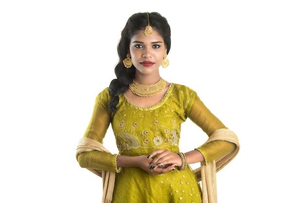 白い壁にポーズをとって美しい伝統的なインドの女の子の肖像画。