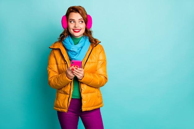 아름 다운 여행자 아가씨의 초상화 보류 전화 관심 측면 빈 공간 착용 유행 캐주얼 노란색 외투 스카프 보라색 바지.