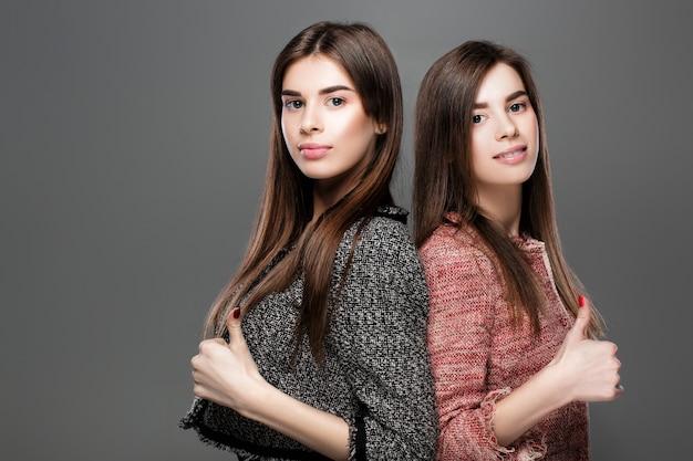 Портрет красивых близнецов женщин показывает палец вверх жест