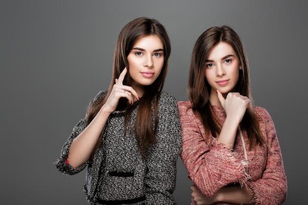 自然なメイクと長い髪の美しい双子の女性の肖像画。ファッション