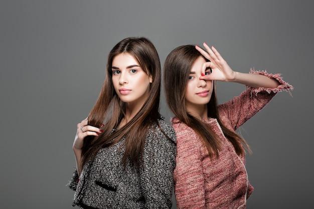 自然なメイクと長い髪の美しい双子の女性の肖像画はジェスチャーokを示しています。