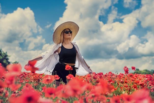 白いブラウスを着て、晴れた日にポピー畑でポーズ、ライフスタイル、ブロンドの髪を持つ美しいウクライナの女性の肖像画