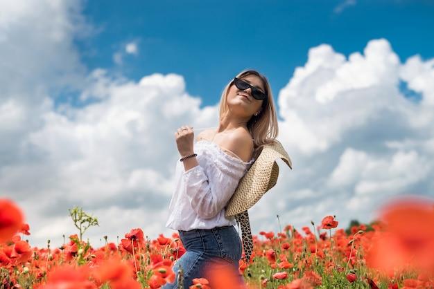 Портрет красивой украинской женщины со светлыми волосами, в белой блузке, позирующей в маковом поле в солнечный день