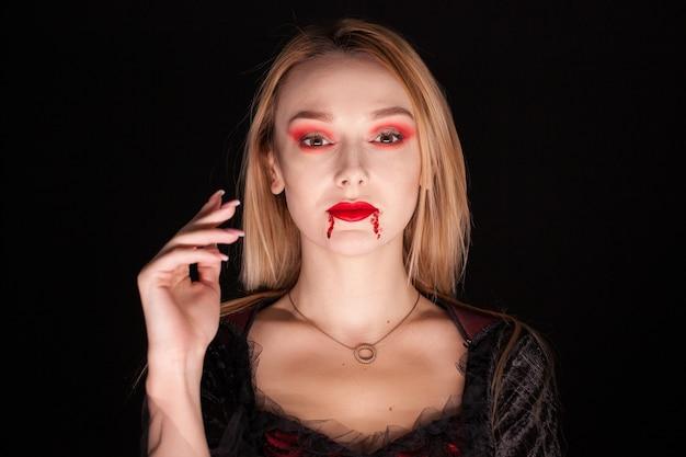 黒の背景の上の美しい吸血鬼の女性の肖像画。魅力的な吸血鬼。