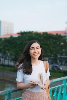 서서 흐림 도시 배경으로 바람에 책을 읽고 아름 다운 베트남 여자의 초상화. 대학에서 행복한 독자.