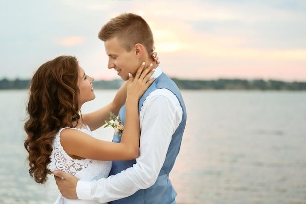 川の近くの美しい結婚式のカップルの肖像画、クローズアップビュー