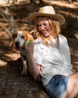 Портрет красивой женщины и ее собаки, играющей