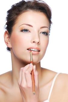 립 컨실러 브러시를 사용하여 립스틱을 적용하는 아름다운 여자의 초상화
