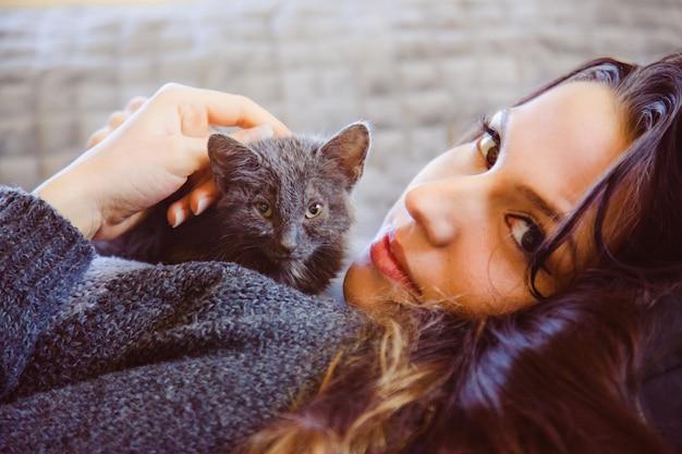 愛撫と通りの猫と遊ぶ美しい女性の肖像画。