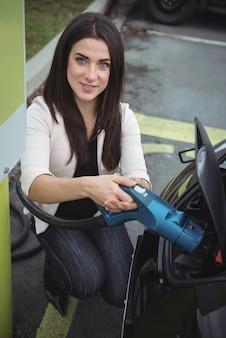 Портрет красивой женщины, заряжающей электромобиль