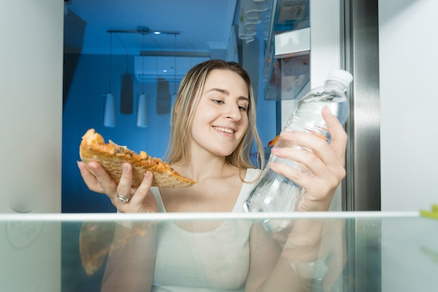 피자와 물 한 병 사이에서 선택하는 아름다운 여성의 초상화. 냉장고 내부의 모습입니다.