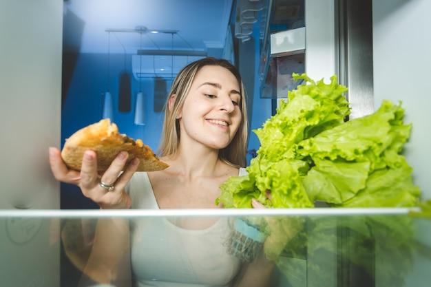 ピザと新鮮なサラダのどちらかを選択する美しい女性の肖像画。冷蔵庫の中からの眺め。健康食品と不健康食品の概念。