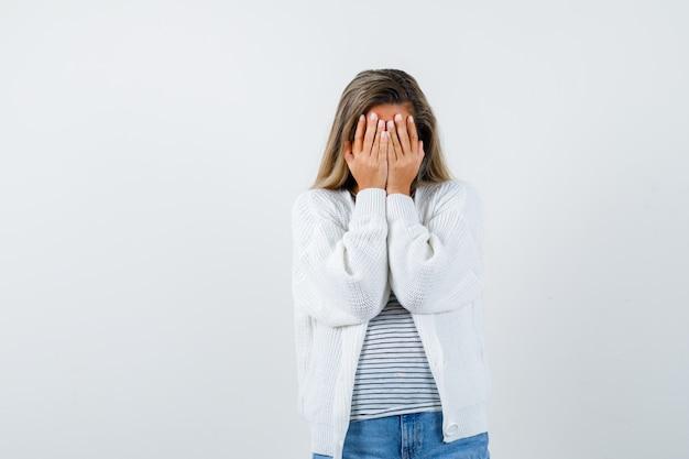 Портрет красивой женщины, закрывающей лицо руками в куртке и грустно смотрящей спереди