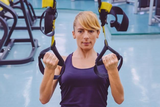フィットネスセンターでフィットネスストラップを使用してハードサスペンショントレーニングをしている美しい女性の肖像画。健康的でスポーティーなライフスタイルのコンセプト。