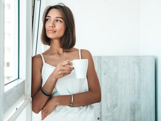 Портрет красивой женщины, одетой в белую пижаму