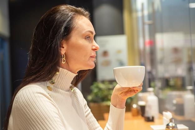カフェのバーでコーヒーを飲む美しい女性の肖像画