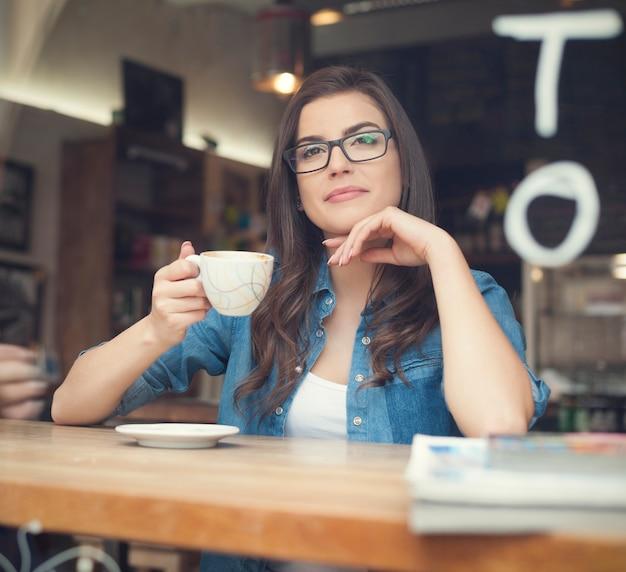 Портрет красивой женщины, пьющей кофе в кафе