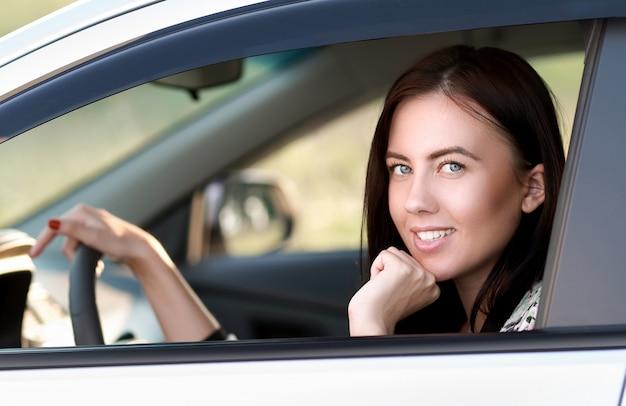 그녀의 차를 운전하는 아름 다운 여자의 초상화