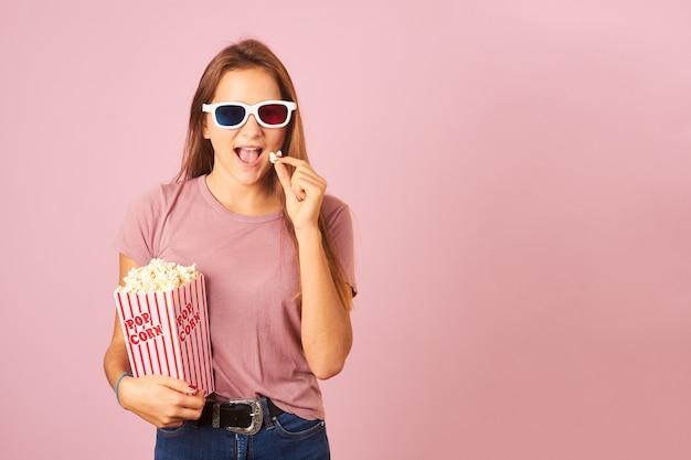 Портрет красивой женщины, едящей попкорн и носящей 3d очки