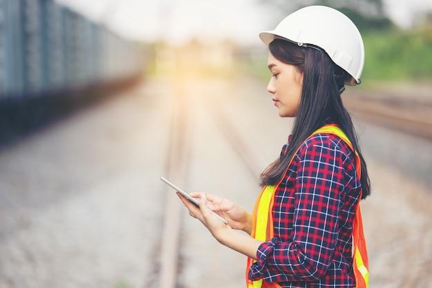 電車のガレージの前でヘルメットを着用したタブレットを使用してエンジニアリングの美しい女性の肖像画。