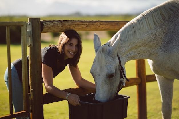 Портрет красивой женщины, кормящей лошадь на сельскохозяйственных угодьях