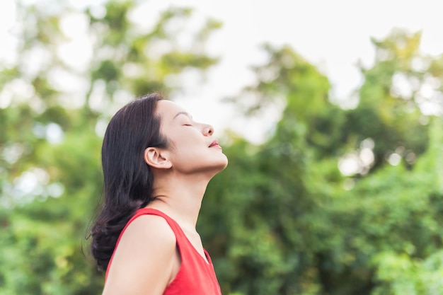Портрет красивой женщины, чувствующей себя живой, дышащей свежим воздухом с закрытыми глазами