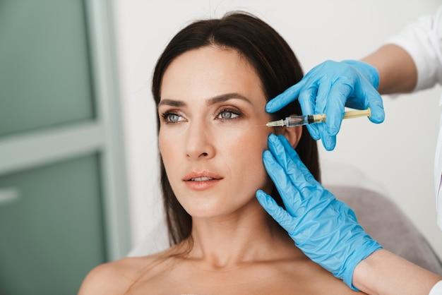 ビューティーサロンで手袋の専門家によって顔にメソセラピー治療を受けている美しい女性の肖像画