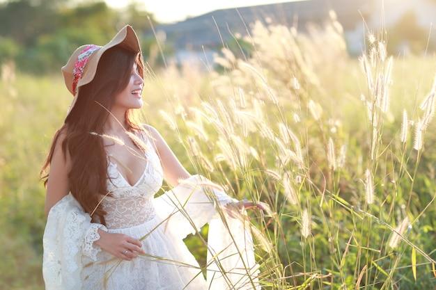 Портрет красивой женщины, имеющие счастливое время и наслаждаясь среди травы поля в природе