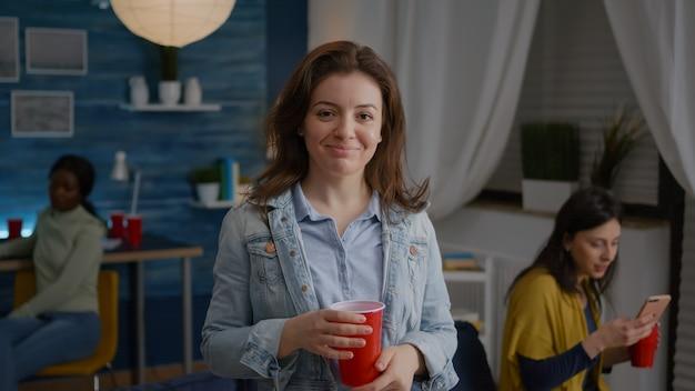 Портрет красивой женщины, держащей стакан пива, глядя в камеру во время ночной вечеринки в фоновом режиме ...