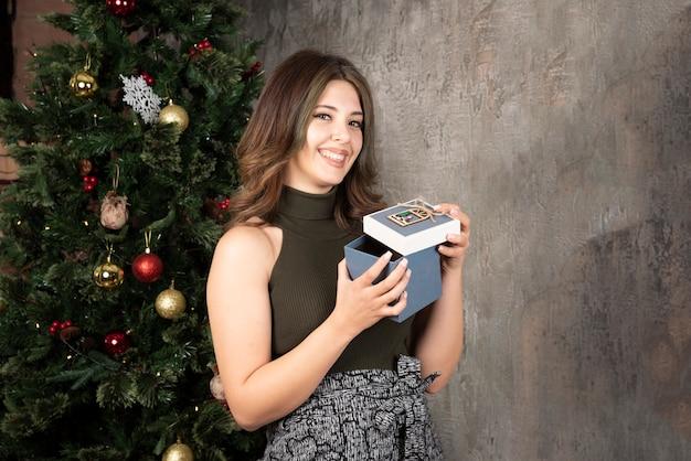 크리스마스 트리 근처에서 행복하게 선물 상자를 들고 있는 아름다운 여성의 초상화