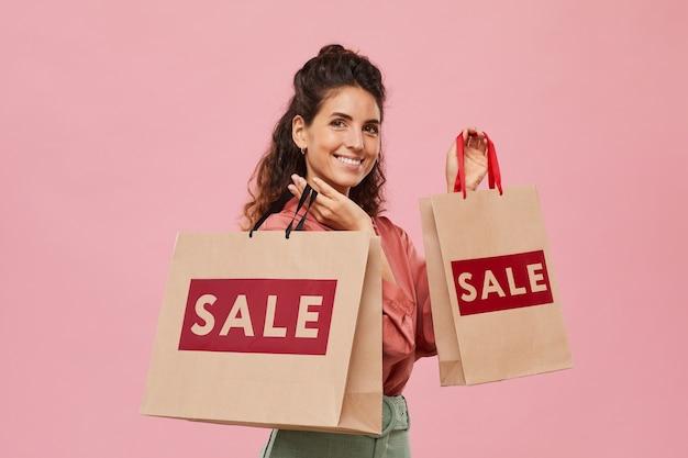 Портрет красивой женщины, держащей хозяйственные сумки и улыбающейся на розовом фоне